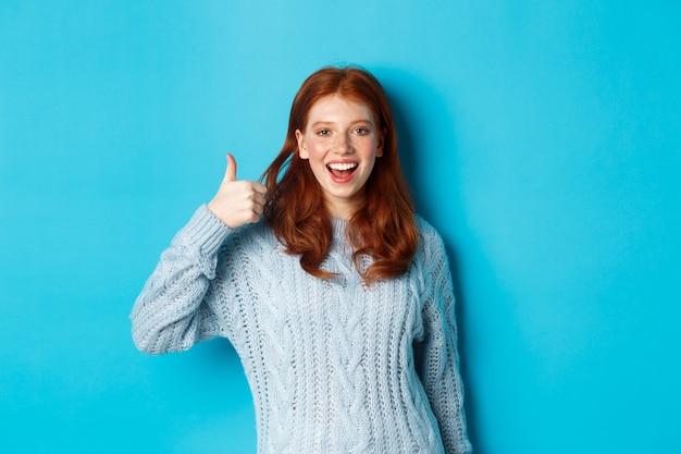 Ragazza rossa allegra in maglione, che mostra il pollice in su in segno di approvazione, come e loda il prodotto, in piedi su sfondo blu.