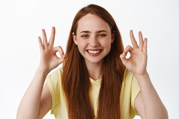 Веселая рыжая девушка с чистой кожей и белыми зубами, улыбаясь и показывая знак ок, хорошо, хвалите хороший выбор, стоя на белом