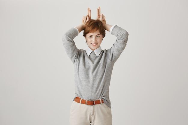 白い壁にポーズをとって短い散髪の陽気な赤毛の女の子
