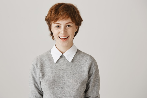 Cheerful redhead girl with short haircut posing against the white wall