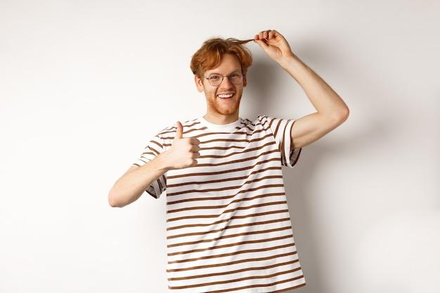 白い背景の上に立って、親指を立てて、新しい色のように彼の赤い髪の毛を見せている陽気な赤毛の男。