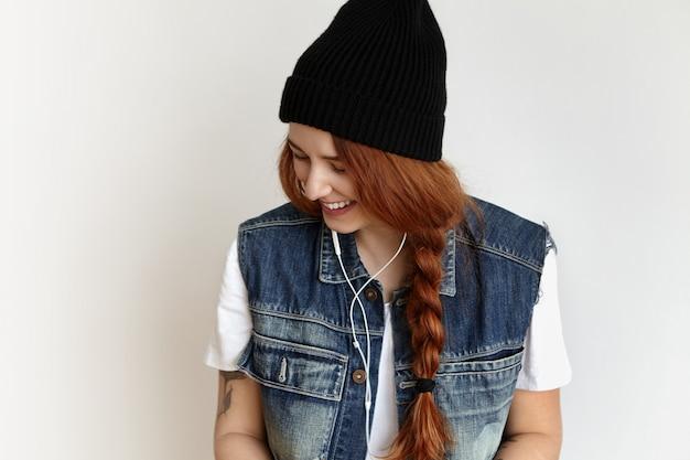 室内で楽しんでファッショナブルな服を着ている陽気な赤毛の内気な少女