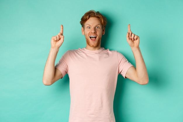 ターコイズブルーの背景の上に立って、指を上に向け、カメラを畏敬の念を持って見つめ、広告を表示しているtシャツの陽気な赤毛の男。