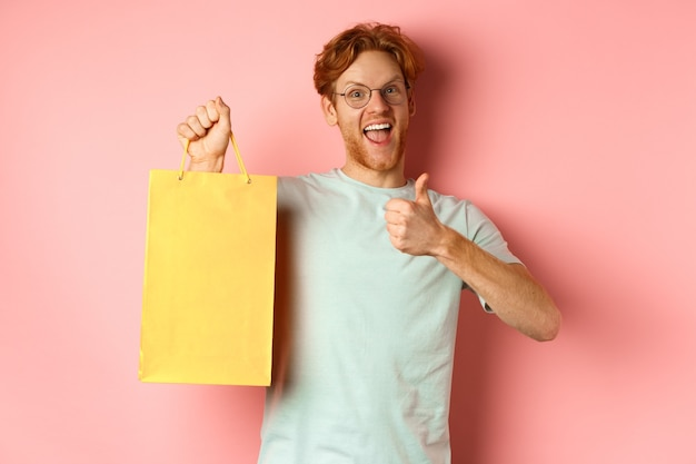 Cheerful redhead man in t-shirt and glasses pointing finger at shopping bag, showing shop with discounts, standing over pink background.