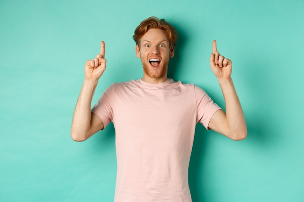 Cheerful redhead man in t-shirt pointing fingers up, staring in awe at camera and showing advertisement, standing over turquoise background.