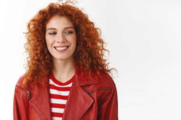 Cheerful redhead modern stylish woman heading work good mood getting hair done curls smiling delighted look aside dreamy lovely memory recalling standing white wall