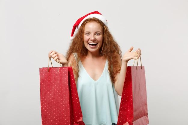 白い背景で隔離のクリスマス帽子の陽気な赤毛サンタの女の子。明けましておめでとうございます2020年のお祝いの休日のコンセプト。コピースペースをモックアップします。買い物の後、ギフトや購入品が入ったパッケージバッグを持ってください。