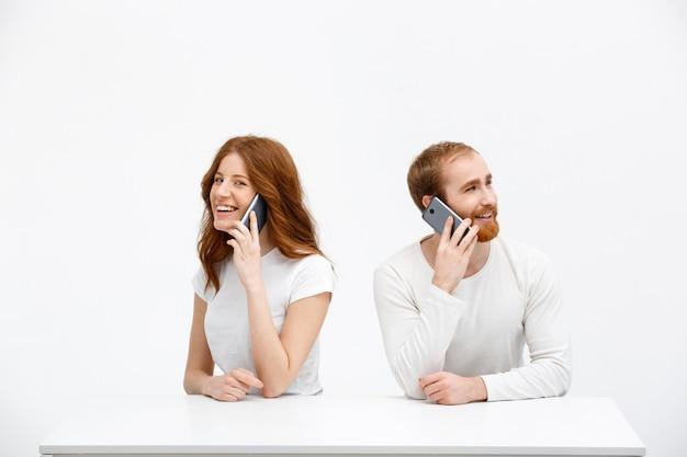 陽気な赤毛の女性と男性、携帯電話の話