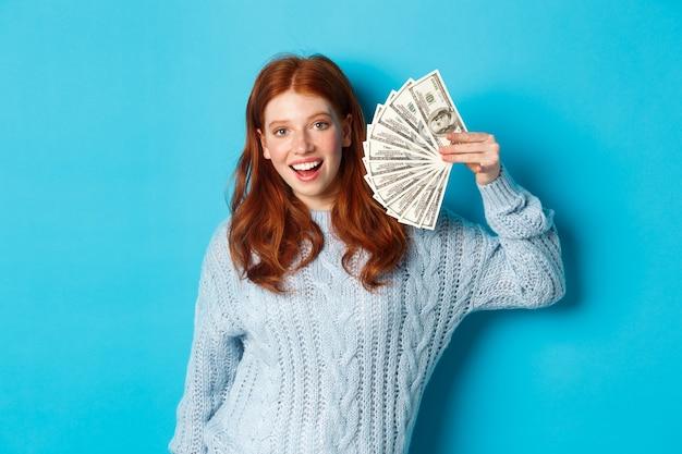 ドルを示し、満足して笑顔でお金を保持し、青い背景の上に立っているセーターの陽気な赤毛の女性。