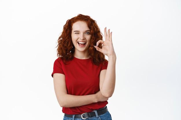 Веселая рыжая женщина с кудрявыми волосами показывает знак ок, подмигивает и улыбается, говорит да, поощряет что-то купить, делает хороший жест, одобряет и хвалит продукт хорошего качества