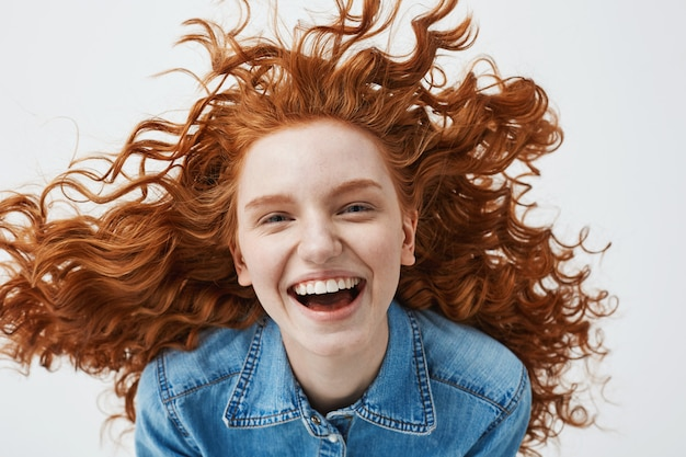 Cheerful redhead woman with flying curly hair smiling laughing.