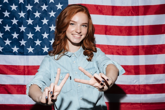 Cheerful redhead young lady showing peace gesture.