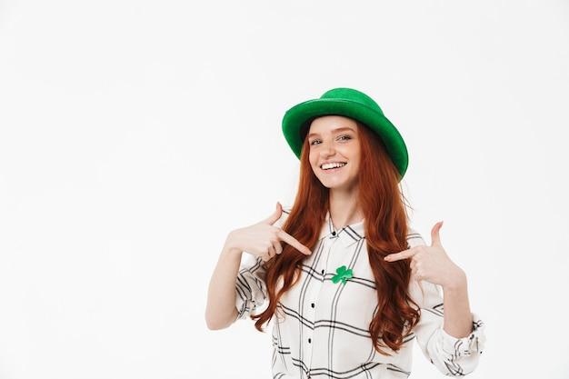 Веселая рыжеволосая девушка в зеленой шляпе стоит изолированно над белой стеной, празднует день святого патрика