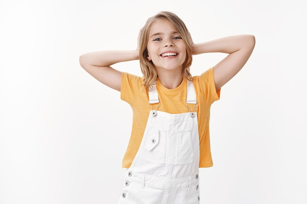 Cheerful relaxed pretty blond little girl chill, lay back and enjoy summer holidays, school-free days weekends, rest on vacation, hold hands behind head lazy pose smiling happily, laughing