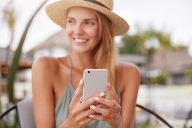 Allegra donna rilassata utilizza smart phone per chattare con gli amici, si siede nella moderna caffetteria o bar con terrazza. la bella donna legge buone notizie sul sito internet, gode del riposo estivo. concentrarsi sul telefono cellulare