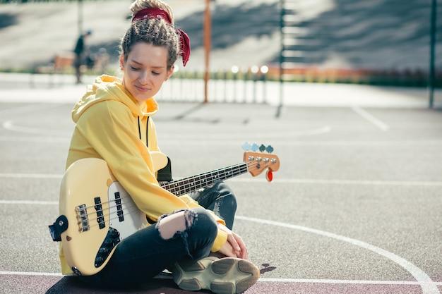 カジュアルな服を着て、ギターで地面に座って笑っている陽気なリラックスした若い女性