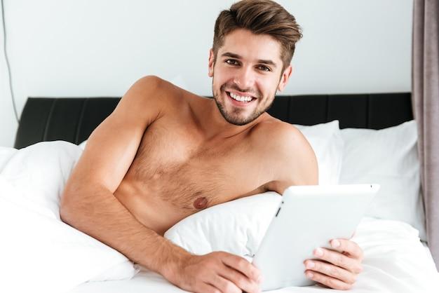 Веселый расслабленный молодой человек, лежащий и использующий планшет в постели