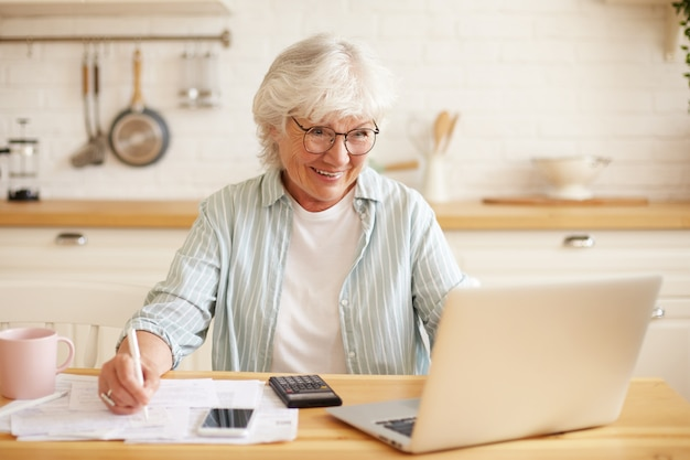 Cheerful retired female accountant working distantly from home using generic portable computer, sitting at kitchen table with calculator and cell phone, holding pencil, making notes in financial docs