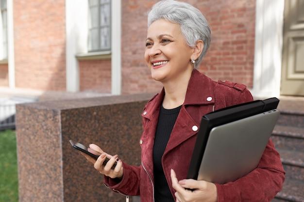 쾌활한 은퇴 한 여성이 휴대용 컴퓨터와 스마트 폰으로 야외에서 포즈를 취하고, 넓게 웃고, 친구를 만나서 행복합니다.