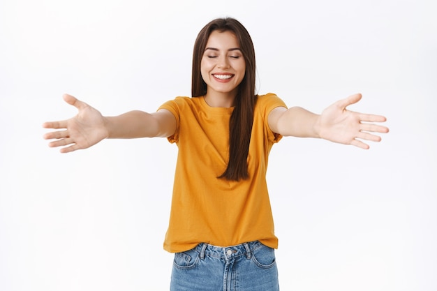 Donna femminile allegra e romantica raggiunge le mani verso la telecamera, allarga le braccia lateralmente per coccolare o abbracciare qualcuno, chiudi gli occhi aspettando che ti avvicini, sorridendo soddisfatto e felice, sfondo bianco