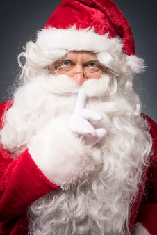 Cheerful santa claus showing a silence sign