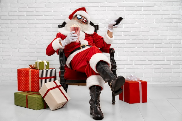 Cheerful santa claus sitting in armchair and watching tv