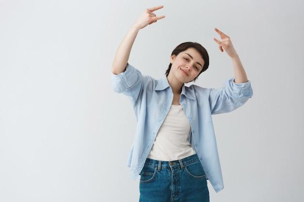 Maschiaccio allegro della ragazza impertinente che fa gesto rock-on, godendo del festival o della festa di musica