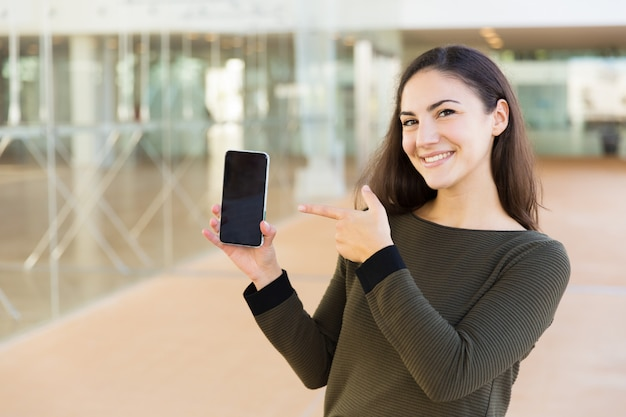 Cheerful satisfied cellphone user introducing new online app