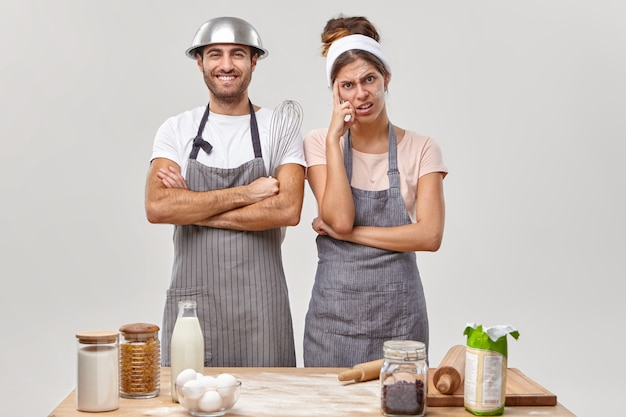 Cheerful satisfied husband in apron glad to help wife with cooking, tired woman thinks how to prepare delicious family recipe cake or dessert, being busy at kitchen. hobby and pastime concept