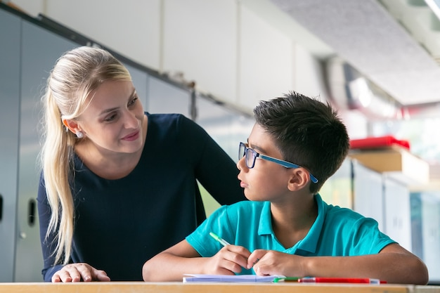 Cheerful school teacher giving help and support to schoolboy in class
