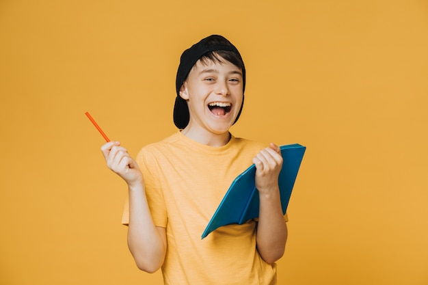 Cheerful schoolboy dressed in yellow t-shirt and black baseball cap, holds his notebook, laughing loudly,. education and youth concept.