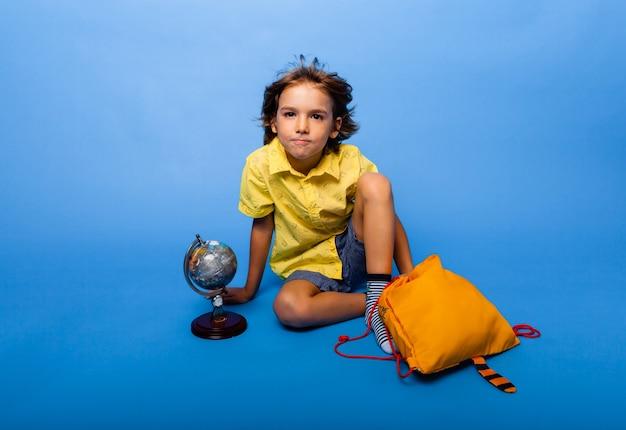 陽気な男子生徒は、バックパックと地球儀と青い背景に座っています。教育の概念