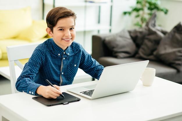 現代のラップトップの前に座って笑っている間、現代の描画パッドとスタイラスを使用して陽気な男子生徒