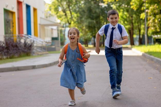 晴れた日の朝、元気な小学生、バックパックを背負った白いシャツを着た女の子と男の子が走ります