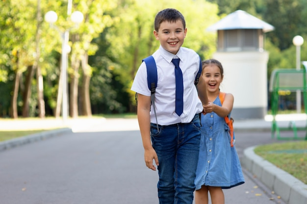 緑の公園を背景に晴れた日の朝にバックパックと白いシャツを着た陽気な小学生の男の子と女の子