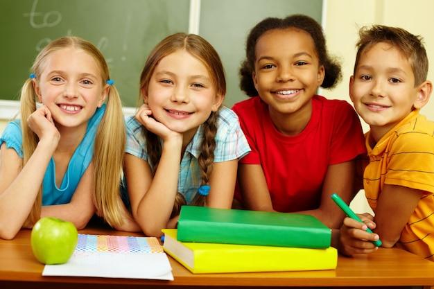 Cheerful schoolchildren with blackboard background