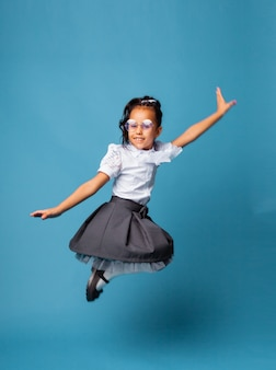 Веселая школьница 7 лет с сумкой через плечо, прыгает на синем фоне.