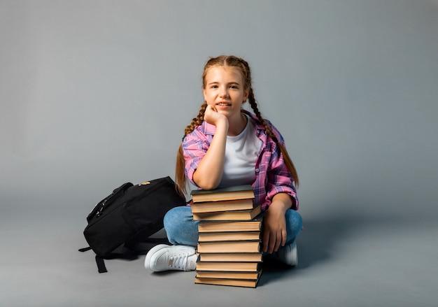 陽気な女子高生は、スタジオの灰色の背景に本のスタックに座っていることを夢見ています。コピースペース