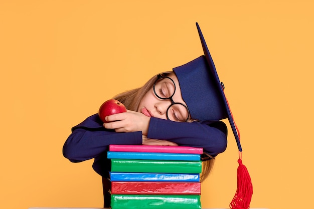 Cheerful schoolgirl in graduation outfit slepping while holding an apple on pile of textbooks