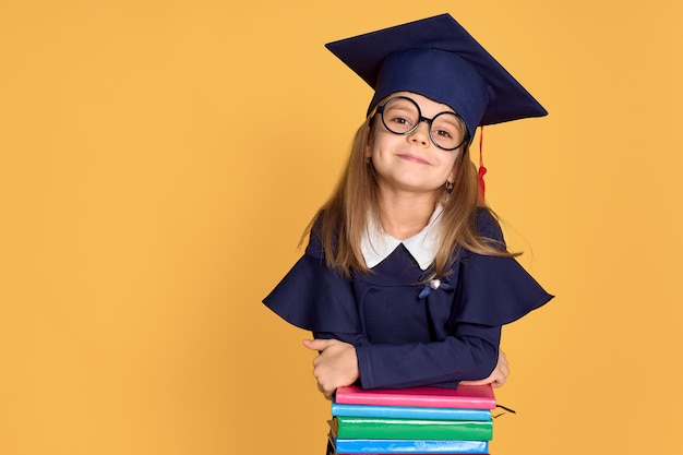 Cheerful schoolgirl in graduation outfit smiling while leaning on pile of textbooks