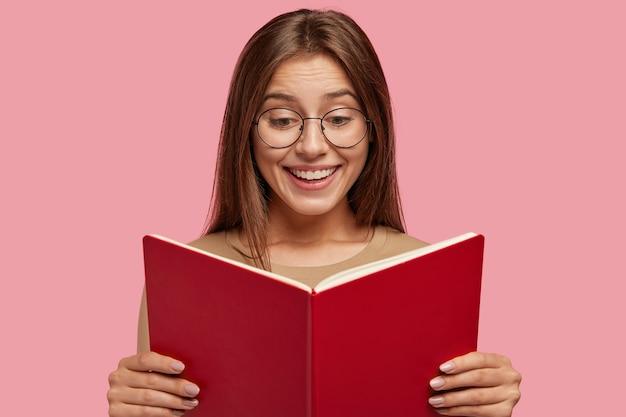 Веселая школьница держит учебник, читает интересную книгу