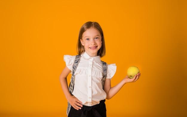 Веселая школьница в белой блузке и с рюкзаком держит зеленое яблоко на желтом фоне с копией космоса