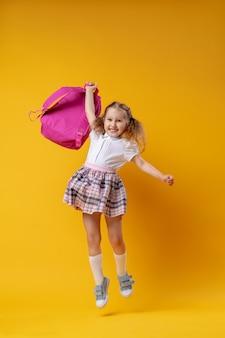 バックパックジャンプと制服を着た陽気な女子高生