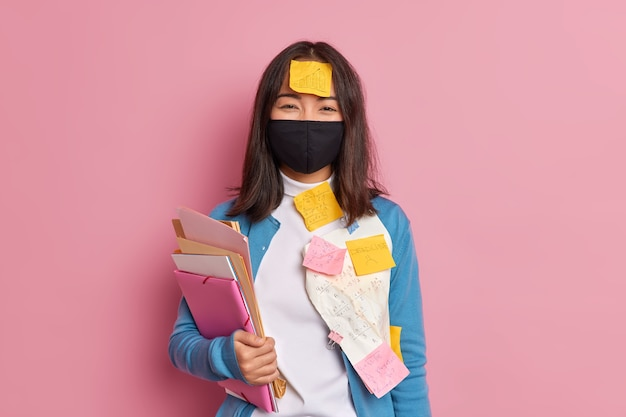 Cheerful schoolgirl learns maths prepares for exams wears black disposable mask to prevent covid 19 makes cribs with mathematical formulas busy working analyzes recieved results.