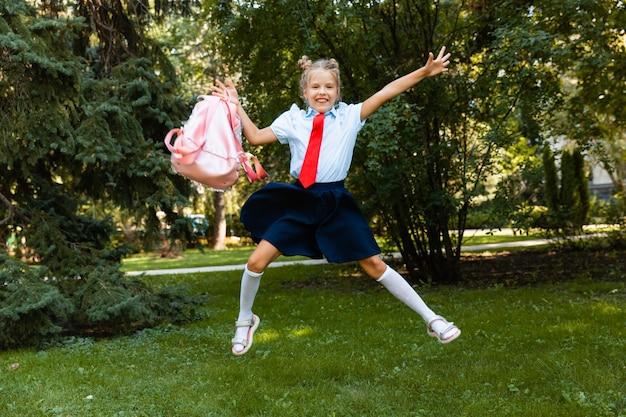 Веселая школьница с розовым рюкзаком прыгает на фоне природы.