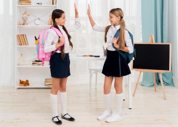 Cheerful schoolgirls giving high five happily