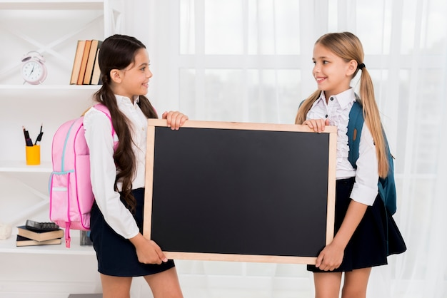 Cheerful schoolgirls with backpacks holding blackboard in room