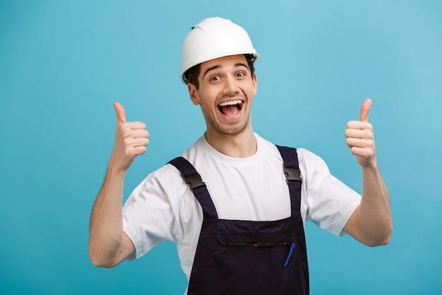 Веселый кричащий мужчина-строитель в защитном шлеме показывает палец вверх над синей стеной