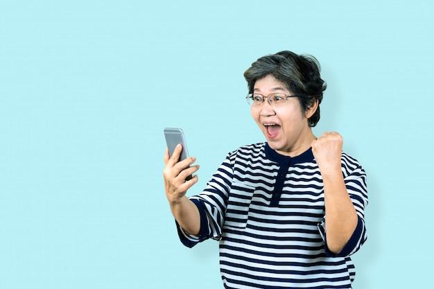 Жизнерадостная старшая азиатская женщина держа и смотря smartphone на изолированной предпосылке чувствуя выигрыш, праздновать и победу. более старый женский образ жизни концепция синий фон.