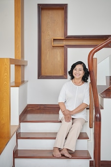 Cheerful senior asian woman sitting on stairs at home